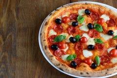 Hoogste mening van Napolitaanse pizza met pepperonis, mozarella, kersentomaten en zwarte olijven op een houten lijst Sluit omhoog stock fotografie