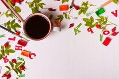 Hoogste mening van ontwerperdesktop met koffiekop, bloemen, potlood Royalty-vrije Stock Afbeeldingen