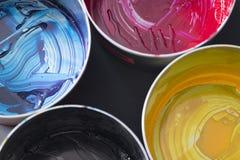 Hoogste mening van oude CMYK-verfblikken op donkere achtergrond Kleurrijke bac Stock Afbeeldingen