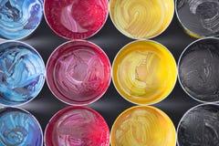 Hoogste mening van oude CMYK-verfblikken op donkere achtergrond Kleurrijke bac Stock Foto's