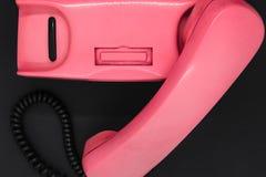Hoogste mening van oude en vuile roze retro telefoon op zwarte oppervlakte als achtergrond stock foto's