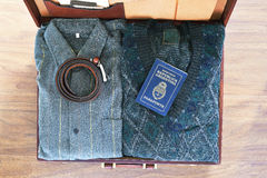 Hoogste mening van oude koffer met kleren en paspoort op houten flo Stock Afbeelding