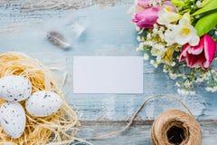 Hoogste mening van paaseieren in de bloemen en de veren van de nestlente over blauwe rustieke houten achtergrond Lege Kaart royalty-vrije stock afbeelding