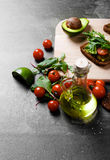 Hoogste mening van plantaardige ingrediënten Fles van olijfolie, tomaten, saladebladeren en sandwiches op de lijstachtergrond royalty-vrije stock foto's