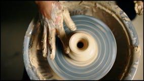 Hoogste mening van pottenbakkershanden die aan aardewerkwiel werken en een pot maken stock video