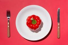 Hoogste mening van rode groene paprika op witte plaat met mes en vork o Stock Afbeelding