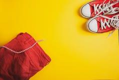 Hoogste mening van rode tennisschoenen en rode borrels op gele achtergrond stock afbeeldingen