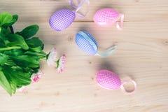 Hoogste mening van roze en blauwe geruite paaseierendecoratie en witte en roze madeliefjes op bleke houten achtergrond stock afbeeldingen