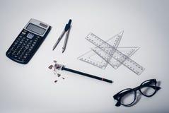 Hoogste mening van schoollevering op schone witte Desktopachtergrond met calculator, document kompas, heersers, glazen en potlood royalty-vrije stock afbeeldingen