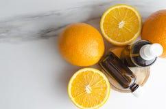 Hoogste mening van sinaasappelen en bootles met schoonheidsmiddelenolie voor lichaamsverzorgingbehandelingen stock afbeeldingen