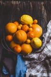 hoogste mening van sinaasappelen, mandarijnen, citroenen, kumquats in plaat en keukenhanddoeken stock fotografie