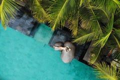 Hoogste mening van slanke jonge vrouw in het beige bikini en strohoed ontspannen dichtbij luxe zwembad en palmen Vakantie stock foto's