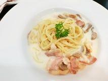 Hoogste mening van spaghetticarbonara met roomsaus, bacon en paddestoelen op witte plaat royalty-vrije stock fotografie
