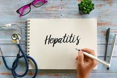 Hoogste mening van stethoscoop, glazen, installatie en van de handholding pen het schrijven Hepatitis op notitieboekje op houten  stock afbeelding