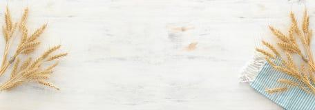 Hoogste mening van tarwegewassen en landelijke keukenhanddoek over witte houten achtergrond Symbolen van Joodse vakantie - Shavuo stock afbeeldingen