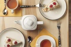 hoogste mening van theepot, twee koppen met hete thee en heerlijke cakes stock foto