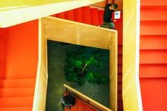 Hoogste mening van twee jongeren met hun mobiele apparaten op de trap binnen van het gebouw - Beeld stock foto