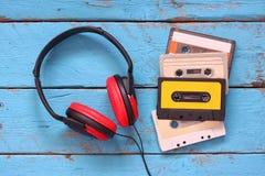 Hoogste mening van uitstekende hoofdtelefoons en cassettes over aqua houten lijst Gefiltreerd Retro Royalty-vrije Stock Afbeeldingen