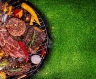 Hoogste mening van vers die vlees en groente bij de grill op gras wordt geplaatst stock foto's