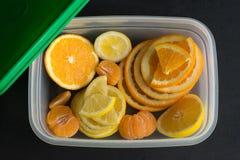 Hoogste mening van verse, gesneden citrusvruchtencitroen, sinaasappel, mandarijn in plastic container op zwarte achtergrond Royalty-vrije Stock Foto's
