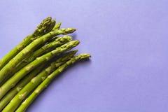 Hoogste mening van verse groene asperge tegen purpere achtergrond met exemplaarruimte royalty-vrije stock afbeeldingen