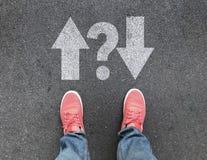 Hoogste mening van voeten en verschillende richtingspijlen met vraagteken op asfaltweg stock foto's