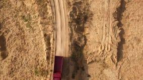Hoogste mening van vrachtwagen het drijven op landelijke weg sc?ne De ritten van de stortplaatsvrachtwagen op droge gele steengro stock footage