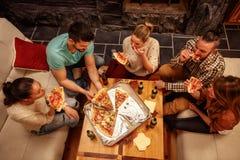 Hoogste mening van vrienden die pizza eten en partij hebben Royalty-vrije Stock Afbeeldingen