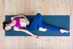 Hoogste mening van vrij magere jonge Kaukasische vrouw die sportkleding dragen die bij mat het ontspannen na training in gymnasti royalty-vrije stock afbeeldingen