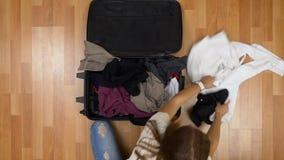 Hoogste mening van vrouw die kleren werpen in en koffer die in zeven haasten sluiten weggaan stock footage