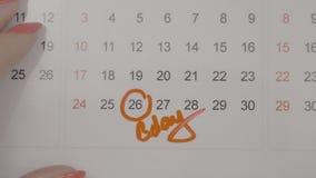 Hoogste mening van vrouwenhanden die geboortedag op kalender ondertekenen en de dagen tellen aan het - stock videobeelden