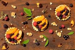 Hoogste mening van wafels, perzik, bes, aardbei en chocolade, honingsdalingen op houten achtergrond Stock Foto's