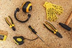 Hoogste mening van werkend hulpmiddel: het lawaai isoleerde hoofdtelefoons, meetlint, gele handschoenen, moersleutel, schroevedra royalty-vrije stock foto