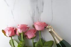 Hoogste mening van wijnfles, roze rozen op witte oppervlakte Romantisch dinerconcept stock foto