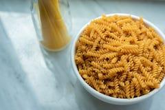 Hoogste mening van witte kom van spiraalvormige macaroni en gebonden spaghettista royalty-vrije stock foto