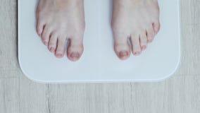 Hoogste mening: vrouwelijke benentribune op digitale slimme schalen, dagelijkse gewichtsmeting stock video