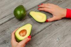 Hoogste mening - vrouwenhand met rode spijkers, die avocado houden in hal wordt gesneden stock fotografie