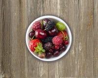 Hoogste mening Vruchten en bessen in kom op houten achtergrond Rijpe bessen, frambozen, kersen, aardbeien, zwarte kruisbessen, royalty-vrije stock afbeeldingen