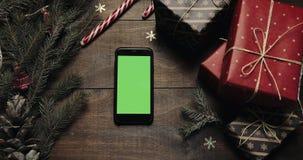 Hoogste mening Zwarte smartphone met het groene scherm die op de lijst met de decoratie van de Kerstmisvakantie liggen de Kerstma stock videobeelden