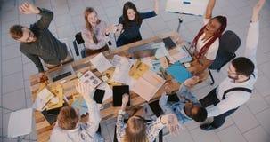 Hoogste menings gelukkig team van collega's die op modern kantoor, toetredende handen en het slaan samenwerken, het vieren succes stock video