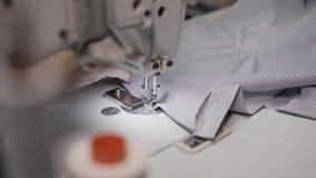 Hoogste menings handbediend schot van volwassen vrouwelijke handen die kant van gestreepte stof naaien stock videobeelden