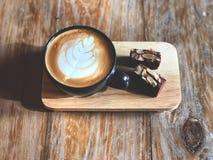 Hoogste menings Heerlijk Ontbijt; De koffie van de Lattekunst in Zwarte die kop en Brownie met gesneden amandel wordt bedekt royalty-vrije stock foto's