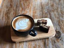 Hoogste menings Heerlijk Ontbijt; De koffie van de Lattekunst in Zwarte die kop en Brownie met gesneden amandel wordt bedekt stock afbeelding
