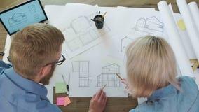 Hoogste menings klein team van architecten die samen met blauwdrukken werken stock videobeelden