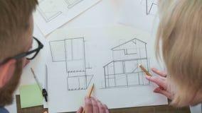 Hoogste menings klein team van architecten die samen met blauwdrukken werken stock video