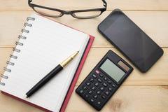Hoogste menings leeg notitieboekje, calculator, pen, glazen en slimme telefoon Royalty-vrije Stock Fotografie