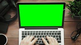 Hoogste menings mannelijke handen die aan laptop computer met het groene hierboven scherm bij wit bureau werken van