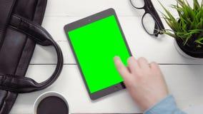 Hoogste menings mannelijke handen die veelvoudige gebaren op digitale tablet met het groene hierboven scherm tonen bij wit bureau stock footage