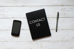 Hoogste menings mobiele die telefoon, pen en notitieboekje met CONTACT de V.S. op witte houten achtergrond wordt geschreven stock afbeeldingen