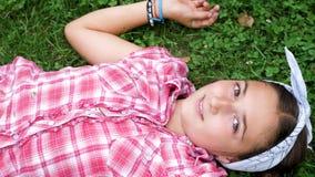 Hoogste menings mooi jong meisje die in het gras liggen stock footage